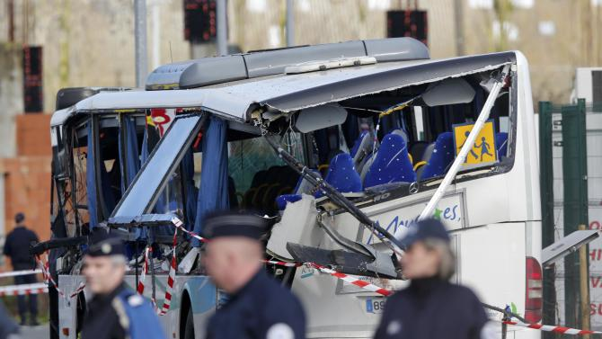 French police work at the scene of the wreckage of a school minibus after it crashed into a metal panel which fell from a truck in Rochefort