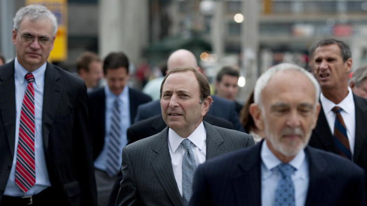 NHL commissioner Gary Bettman, center, arrives with members of his negotiating team for collective bargaining talks in Toronto on Tuesday, Aug. 14, 2012. Negotiations continue between the league and the NHLPA to avoid a potential lockout. (AP Photo/The Canadian Press, Chris Young)
