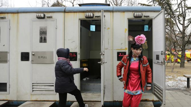 A male folk artist dressed as a traditional Chinese woman walks out of a mobile toilet in Beijing