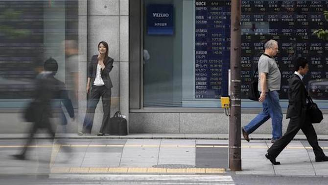 Pedestrians walk past a stock quotation board displaying stock prices outside a brokerage, in Tokyo June 14, 2013. REUTERS/Yuya Shino/Files