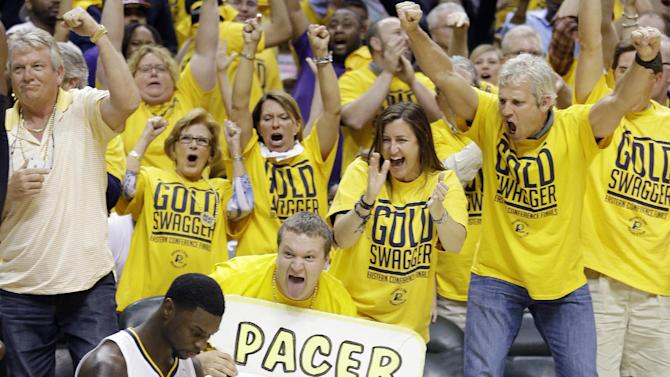 Indiana Pacers fans react after Lance Stephenson, sitting, made a shot against the Miami Heat as time expired in the third quarter of Game 4 of the NBA basketball Eastern Conference finals, Tuesday, May 28, 2013, in Indianapolis. (AP Photo/Michael Conroy)