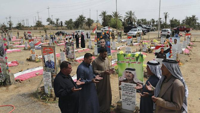 In this Wednesday, March 25, 2015, photo, Sunni men from the al-Jabouri tribe pray at a grave for their fellow tribesman killed in a battle with Islamic State militants, in the town of Duluiyah, 45 miles (75 kilometers) north of Baghdad, Iraq. Sunni tribes that have stood up to the IS group have paid a heavy price, and anger at the Shiite-led government runs deep in the areas of northern and western Iraq that now make up the extremist group's self-styled caliphate. (AP Photo/Karim Kadim)