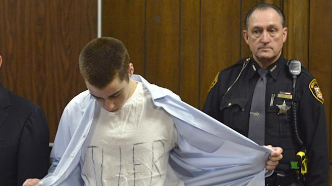 T.J. Lane unbuttons his shirt during sentencing Tuesday, March 19, 2013, in Chardon, Ohio.  Lane was given three lifetime prison sentences without the possibility of parole Tuesday for opening fire last year in a high school cafeteria in a rampage that left three students dead and three others wounded.  Lane, 18, had pleaded guilty last month to shooting at students in February 2012 at Chardon High School, east of Cleveland. Investigators have said he admitted to the shooting but said he didn't know why he did it. Before the case went to adult court last year, a juvenile court judge ruled that Lane was mentally competent to stand trial despite evidence he suffers from hallucinations, psychosis and fantasies. (AP Photo/The News-Herald, Duncan Scott, Pool)