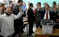 Muslim Brotherhood candidate Mohammed Mursi casts his ballot at a polling station in the city of Zagazig, 90 kms north of Cairo in the eastern part of the Nile Delta. Egyptians voted on Saturday in a run-off presidential election pitting an Islamist against Hosni Mubarak's last premier as the military rulers entered a showdown with the Islamists by disbanding parliament