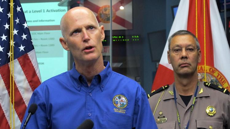 Florida Gov. Rick Scott announces a state of emergency for most of Florida's Gulf coast due to heavy rains and flooding caused by Tropical Storm Debby during a news conference at the State Emergency Operations Center in Tallahassee, Fla.  Col. David Brierton, commander of the Florida Highway Patrol, right, listens. Tropical Storm Debby drenched Florida with heavy rains, flooded low-lying neighborhoods and knocked out power to thousands of homes and businesses as it lingered off the state's coast Monday. (AP Photo/Bill Cotterell)