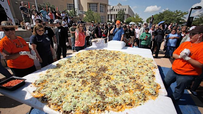 "In this Saturday Sept. 10, 2011 photo released by the New Mexico Tourism Department, residents help build what state officials are calling the ""world's largest Navajo taco,"" in Gallup, N.M. Organizers say no world record exists for the largest Navajo taco so they built one using 150 pieces of fry bread and 30 pounds of green chile. According to volunteers and state officials, the Navajo taco created Saturday was more than 10 feet in diameter and also needed 65 pounds of ground beef, 65 pounds of beans, 50 pounds of lettuce and 90 pounds of cheese. (AP Photo/New Mexico Tourism Department)"