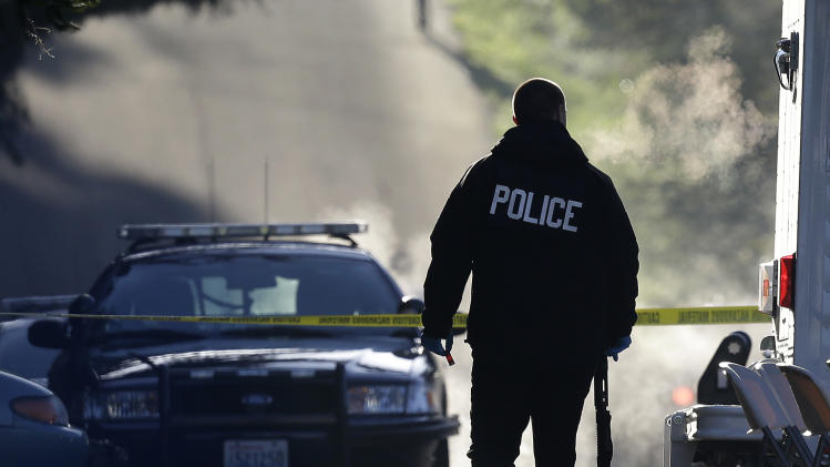A police officer carries a shotgun and what appears to be a shell casing as officers collect evidence from the scene of an overnight shooting that left five people dead, including a suspect who was shot by arriving officers, at an apartment complex in Federal Way, Wash., early Monday, April 22, 2013. (AP Photo/Ted S. Warren)