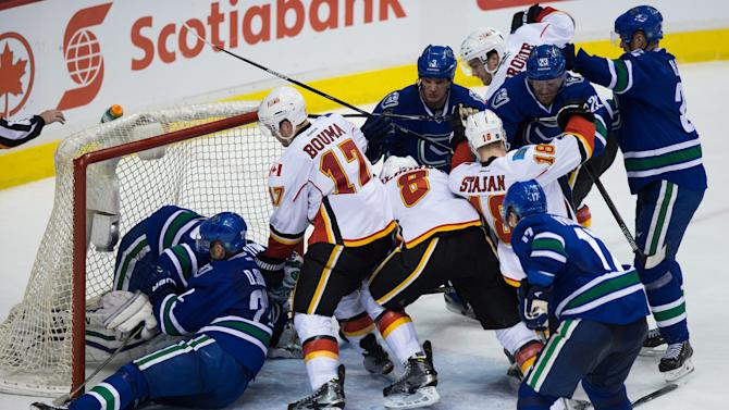 Calgary Flames' Lance Bouma (17), Joe Colborne (8), Matt Stajan (18) and T.J. Brodie, top right, battle Vancouver Canucks' Kevin Bieksa (3), Alexander Edler (23), of Sweden, and Henrik Sedin (33), of Sweden, as Radim Vrbata (17), of the Czech Republic, watches while goalie Ryan Miller, left, covers up the puck as teammate Daniel Sedin (22), of Sweden, slides into him during the second period of an NHL hockey game in Vancouver, British Columbia, on Saturday, Dec. 20, 2014. (AP Photo/The Canadian Press, Darryl Dyck)
