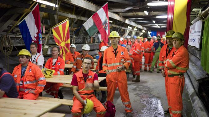"""Miners wait  prior to the tunnel drilling machine """"Sissi"""" breaks through the last section of the Gotthard Base Tunnel near Faido in the canton of Tessin, Switzerland, Oct. 15, 2010. With 57 kilometers (35-miles) the new St. Gotthard tunnel is the world's longest tunnel. The 13.157 billion Swiss franc (9.6 billion euros, 13.6 billion US dollars) Alptransit project, which is due to be operational in 2017, constitutes the center piece of the New Railway Link through the Alps. Engineers are expected to start up the massive drilling machine - nicknamed Sissi -  at 2 p.m. (1200 GMT; 8 a.m. EDT) so it can chew through the last remaining rock separating the two ends of the 57-kilometer (35.4-mile) Gotthard Base Tunnel.  (AP Photo/Keystone/Martin Ruetschi)  **NO SALES, NO ARCHIVES **"""