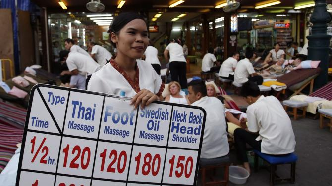 An employee displays a placard advertising massage prices in a tourist district of Khao San Road in Bangkok