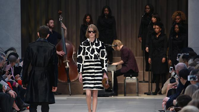 A model wears a design created by Burberry Prorsum, as British musician Tom Odell performs on the piano, during London Fashion Week, at Kensington Gardens in west London, Monday, Feb. 18, 2013. (Photo by Joel Ryan/Invision/AP)