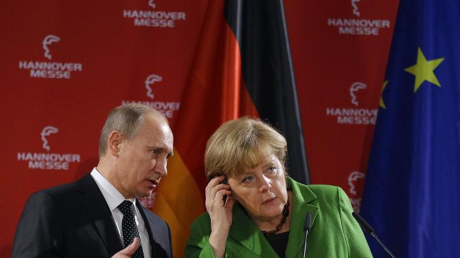 Russian President Vladimir Putin and German Chancellor Angela Merkel address the media during the opening of the  Hannover Fair in Hannover, Germany, Monday, April 8, 2013. (AP Photo/Frank Augstein)