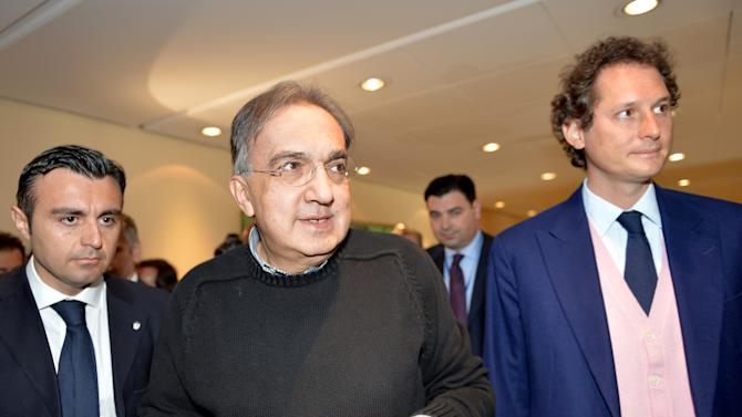 Fiat Chairman John Elkann, right, and Fiat and Chrysler CEO Sergio Marchionne arrive for a meeting with shareholders in Turin, Italy, Monday, March 31, 2014. Fiat and Chrysler CEO Sergio Marchionne says the combined automaker aims to sell 4.5 million to 4.6 million cars this year. Marchionne addressed the last Fiat shareholders' meeting on Monday at the Italian carmaker's historic headquarters in Turin, Italy. The CEO aims to complete the merger of Fiat with U.S. carmaker Chrysler this year to create Fiat Chrysler Automobiles, the seventh-largest automaker with 4.4 million sales last year. (AP Photo/Massimo Pinca)