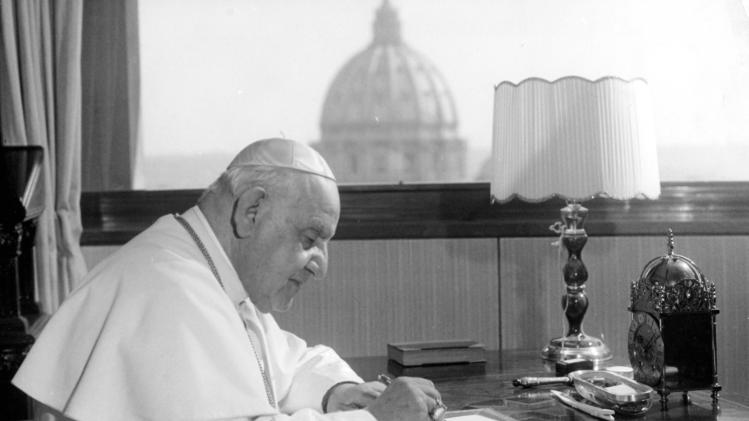 """FILE - In this April 15, 1963 file photo, Pope John XXIII sits at his working desk in his studio in a IX century tower in the Vatican gardens. In background the dome of St. Peter's Basilica. The Pontiff found the tower - once a fortress and later the Vatican observatory - abandoned and in decay. He liked it, particularly for the beautiful view from its covered terrace, embracing a great part of Rome and the surrounding country, in clear weather as far as the sea, distant about 25 kilometers (16 miles). He had it repaired and spends many days working in the studio he has had arranged there. While much of the focus of Sunday's dual canonization will be on Pope John Paul II's globe-trotting, 26-year papacy and his near-record sprint to sainthood, many older Catholics will be celebrating the short but historic pontificate of the """"Good Pope,"""" John XXIII. (AP Photo/Luigi Felici, File)"""
