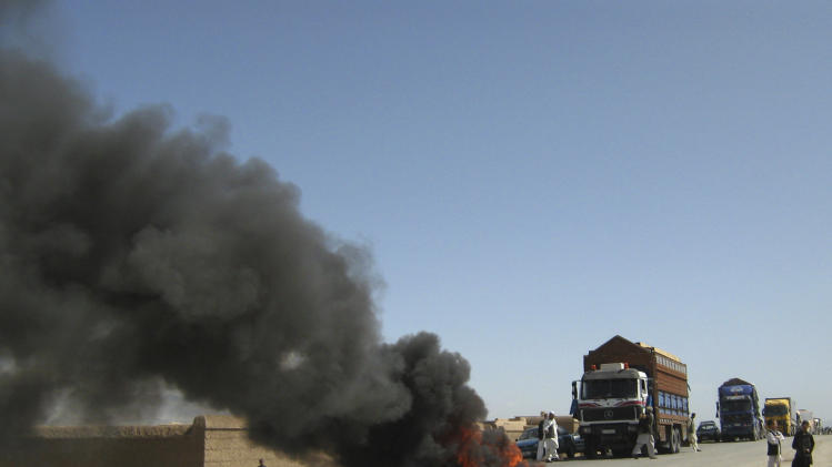 Burning tires block a highway between Kabul and Kandahar in Seed Abad, Wardak province, Afghanistan, Saturday, May 26, 2012. More then 1500 Afghan protesters demanded a stop to military night operations. (AP Photo/Rahmatullah Nikzad)