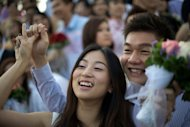 <p>A newlywed couple celebrates after a mass wedding in conjunction with the date 12/12/12 at a Chinese temple in Kuala Lumpur on December 12. Authorities in Hong Kong and Singapore respectively said 696 and 540 couples were scheduled to attend marriage registries, continuing a trend which has seen couples flocking to marry on 11/11/11 and 10/10/10 in both cities.</p>