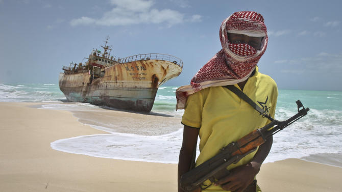 In this photo taken Sunday, Sept. 23, 2012, masked Somali pirate Hassan stands near a Taiwanese fishing vessel that washed up on shore after the pirates were paid a ransom and released the crew, in the once-bustling pirate den of Hobyo, Somalia. The empty whisky bottles and overturned, sand-filled skiffs that litter this shoreline are signs that the heyday of Somali piracy may be over - most of the prostitutes are gone, the luxury cars repossessed, and pirates talk more about catching lobsters than seizing cargo ships. (AP Photo/Farah Abdi Warsameh)