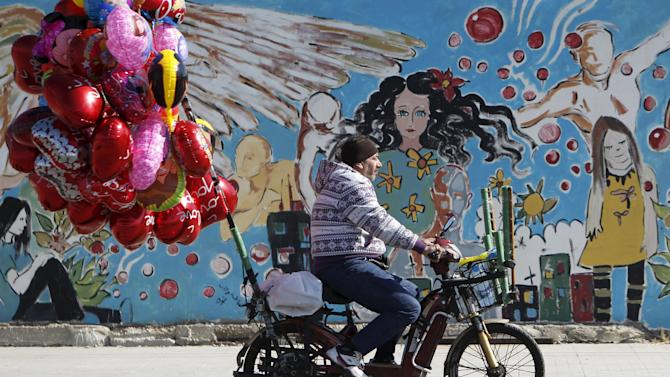 A street vendor sell heart-shaped balloons as he rides a motorbike ahead of Valentine's Day in Sidon