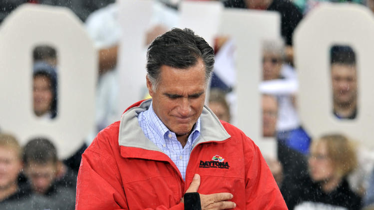 Republican presidential candidate, former Massachusetts Gov. Mitt Romney puts his hand on his heart during a moment of silence for the embassy officials killed in Libya, as he campaigns in the rain at Lake Erie College in Painesville, Ohio, Friday, Sept. 14, 2012. (AP Photo/David Richard)
