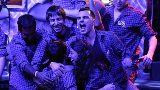 Jake Balsiger, center, is congratulated by friends after doubling up his earnings after raising all in and winning on a pair of Kings during the World Series of Poker Final Table event, Monday, Oct. 29, 2012, in Las Vegas. (AP Photo/Julie Jacobson)