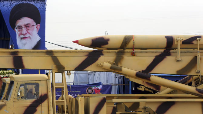 In front of a portrait of the Iranian Supreme Leader Ayatollah Ali Khamenei, a missile is displayed by Iran's army in a military parade marking National Army Day in front of the mausoleum of the late revolutionary founder Ayatollah Khomeini just outside Tehran, Iran, Friday, April 18, 2014. Ahead of the parade Iran's President Hassan Rouhani underscored his moderate policies and outreach to the West in a speech. (AP Photo/Vahid Salemi)