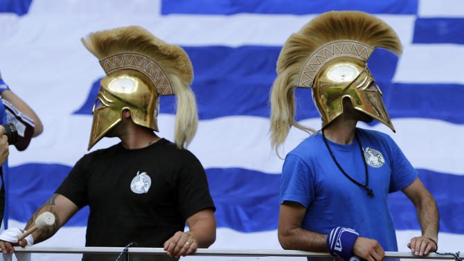 Fans wear mock ancient Greek helmets prior to the Euro 2012 soccer championship Group A  match between Greece and Russia in Warsaw, Poland, Saturday, June 16, 2012. (AP Photo/Thanassis Stavrakis)