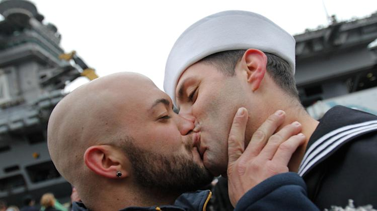"FILE - In this March 2, 2012 file photo, Sean Sutton, left, greets his boyfriend of 2 years, U.S. Navy sailor Jonathan Jewell, E5, with a kiss after Jewell returned from a seven month deployment aboard the USS Stennis in Bremerton, Wash.  Defense Secretary Leon Panetta is thanking gay military members for their service, as the Pentagon prepares to mark June as gay pride month with an official salute.  In a video message to the troops Friday, June 15, 2012, Panetta says that with the repeal last year of the ""Don't Ask, Don't Tell"" law that prohibited gays from serving openly in the military, gays and lesbians can now be proud to be in uniform. (AP Photo/seattlepi.com, Joe Dyer)  MAGS OUT; NO SALES; SEATTLE TIMES OUT; TV OUT; MANDATORY CREDIT"