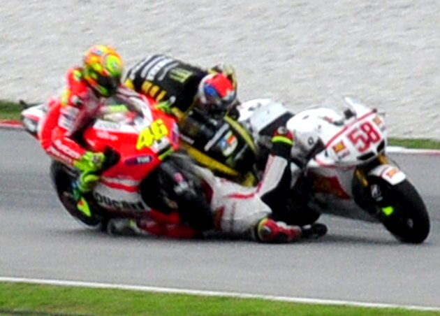Crash between Colin Edwards, center, Valentino Rossi from Italy, left,  and Marco Simoncelli from Italy is seen at turn 11 during the Malaysian MotoGP Grand Prix in Sepang, Malaysia, Sunday, Oct. 23,