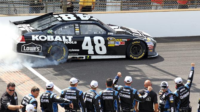 Jimmie Johnson does a burnout in front of his crew after winning the NASCAR Sprint Cup Series Brickyard 400 auto race at the Indianapolis Motor Speedway in Indianapolis, Sunday, July 29, 2012. (AP Photo/Dave Parker)
