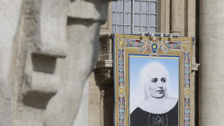 The tapestry of Laura di Santa Caterina da Siena Montoya of Colombia hangs from a balcony in St. Peter's Square at the Vatican prior to the start of the canonization ceremony led by Pope Francis Sunday, May 12, 2013. The pontiff will canonize, Laura di Santa Caterina da Siena Montoya, Antonio Primaldo and his companions, also known as the Martyrs of Otranto, and Maria Guadalupe Garcia Zavala of Mexico in a ceremony at the Vatican on Sunday. (AP Photo/Alessandra Tarantino)