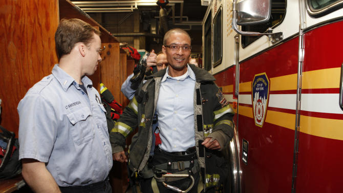 FDNY Lt. James Amsterdam and FDNY Captain David Drake help Director of Brand Management Sports Nutrition for EPIQ Brent Coward get into firemen gear at EPIQ Thank You In Relief of Sandy on Tuesday, February 5, 2013 in New York City. (Photo by Amy Sussman/Invision for EPIQ/AP Images)