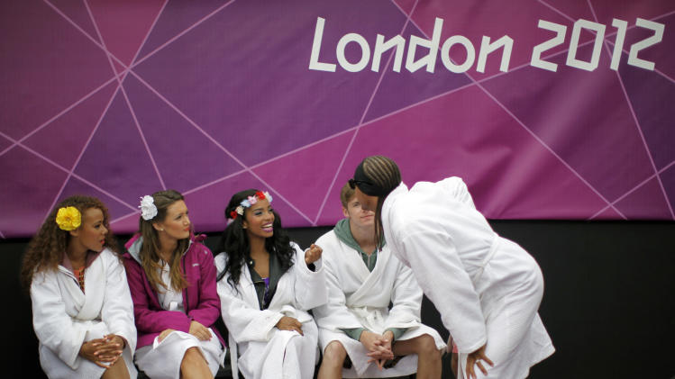 Dancers, wearing robes to keep themselves warm from the cold, wait outside the court before their performance at halftime at the London 2012 Olympic Games at Horse Guards Parade