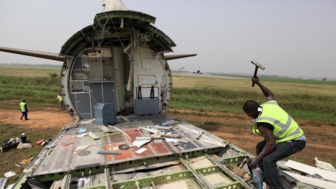 A worker dismantles an abandoned aircraft at Murtala Muhammed International Airport in Lagos, Nigeria, Thursday, Jan. 31, 2013. Nigerian aviation officials have begun trying to dismantle and remove the hulks of abandoned airplanes from airports around the country. Officials say there are least 65 abandoned planes at the country's airports, with at least 13 at Lagos' international airport. (AP Photo/Jon Gambrell)