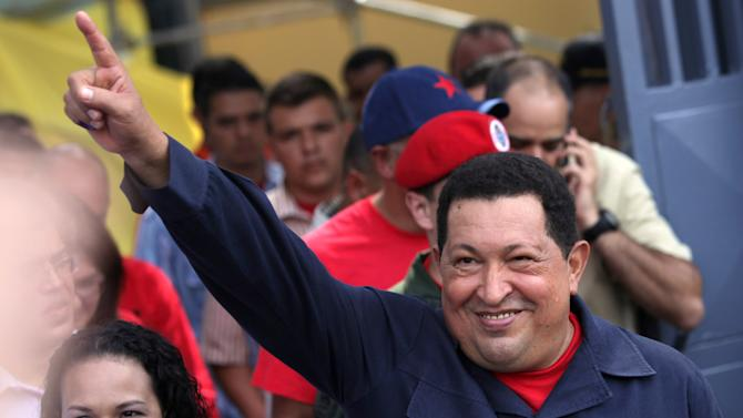 Accompanied by his daughter Rosa Virginia, left, Venezuela's President Hugo Chavez gestures to supporters as he leaves the polling station after voting in the presidential election in Caracas, Venezuela, Sunday, Oct. 7, 2012. Chavez is running for re-election against opposition candidate Henrique Capriles.  (AP Photo/Rodrigo Abd)