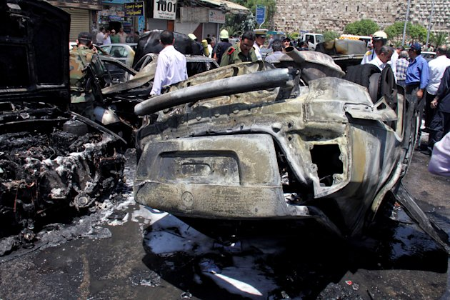 Burnt out cars are seen at the site of a blast in the Syrian capital Damascus Thursday June 28, 2012. A strong explosion rocked the Syrian capital Thursday near a busy market and the Palace of Justice, sending black smoke billowing into the sky. State TV reported at least three people were wounded and around 20 cars were damaged. (AP Photo/Bassem Tellawi)