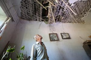 A man examines destruction in his house as a result…