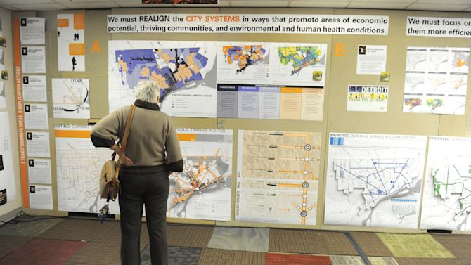 "Mary Egan Price, of Detroit, looks at a vast display for  ""Detroit Future City""  presented  during a news conference at the DWPLTP Homebase on Wednesday, Jan. 9, 2013. The presentation introduces a framework for future decision making for the city. (AP Photo/The Detroit News, Max Ortiz)"