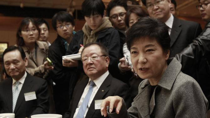 In this photo taken Wednesday, Oct. 31, 2012, ruling Saenuri Party presidential candidate Park Geun-hye, right, talks with South Korean business leaders during a financial strategy forum in Seoul, South Korea. Park attempts to become the country's first female president and keep the government in conservative hands in the Dec. 19 election. She has been in the public eye longer than either of her rivals and is a skilled political operator, but she is also hounded by her late father Park Chung-hee's complicated legacy, which continues to divide many South Koreans. (AP Photo/Ahn Young-joon)