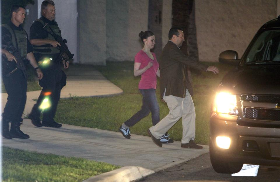 Casey Anthony, center, walks to a SUV with her lawyer Jose Baez after her release from the Orange County Jail in Orlando, Fla., early Sunday, July 17, 2011.  Anthony was acquitted last week of murder in the death of her daughter, Caylee. (AP Photo/John Raoux)