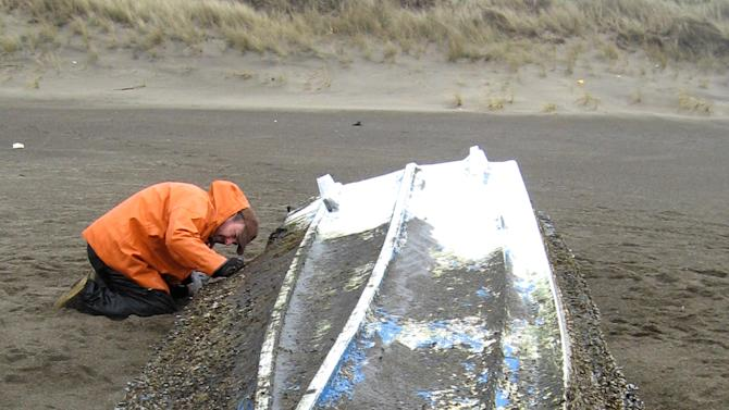 FILE - In this undated photo provided by the Oregon Department of Fish and Wildlife, Justin Ainsworth, Oregon DFW biologist, inspects a boat that washed up on Gleneden Beach, Ore. Scientists say the 30-foot boat that washed ashore on the central Oregon coast appears to be debris from the March 2011 Japan tsunami. The five West Coast states affected by debris from the 2011 tsunami in Japan are about to receive an initial $250,000 each from a $5 million gift from Japan for cleanup. The National Oceanic and Atmospheric Administration is distributing the money to Alaska, California, Hawaii, Oregon and Washington and will allocate the remainder as additional needs arise (AP Photo/Oregon Department of Fish and Wildlife, File)