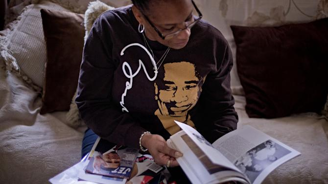 This Jan. 2, 2013, photo, shows Victoria Wimberley, who will be attending President Barack Obama's inauguration for the second time, looking over some of the memorabilia in her home in Decatur, Ga. Four years and one re-election after his historic oath-taking as America's first black president, some of the thrill for Barack Obama is gone. Wimberley brought four busloads of people to Washington for the 2009 inauguration. She's coming again this month, though with two fewer buses, which she blamed on the high price for accommodations, not any lack of excitement for Obama. (AP Photo/David Goldman)
