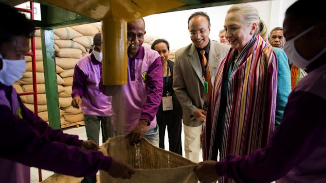 U.S. Secretary of State Hillary Rodham Clinton, 2nd right, watches coffee beans come out of a sorter during a tour of the Timor Coffee Cooperative in Dili, East Timor Thursday, Sept. 6, 2012. U.S. Secretary of State Hillary Rodham Clinton is in East Timor to offer the small half-island nation support as it ends its reliance on international peacekeepers. (AP Photo/Jim Watson, Pool)