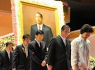 Unification Church devotees stand in front of a portrait of the late Sun Myung Moon as they mourn his death at the church headquarters in Gapyeong. The atmosphere was sombre but calm, as Hyung-Jin Moon, Moon's youngest son and successor, received the mourners