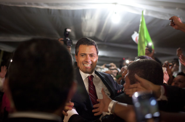 Enrique Pena Nieto, presidential candidate for the Revolutionary Institutional Party (PRI), greets supporters at his party&#39;s headquarters in Mexico City, early Monday, July 2, 2012. Mexico&#39;s old guard sailed back into power after a 12-year hiatus Sunday as the official preliminary vote count handed a victory to Pena Nieto, whose party was long accused of ruling the country through corruption and patronage. (AP Photo/Alexandre Meneghini)