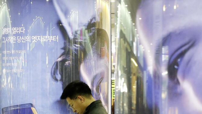 A man uses his smartphone in front of advertisements for Samsung Electronics' Galaxy Note Edge at a subway station in Seoul, South Korea, Thursday, Jan. 29, 2015. Samsung Electronics Co. said Thursday its quarterly earnings dropped to a smaller-than-expected 27 percent in the fourth quarter but its forecast-beating profit could not mask that it was losing the battle of the big phones with Apple Inc. (AP Photo/Ahn Young-joon)