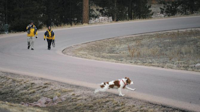 Searchers use a dog Wednesday, March 20, 2013 to search the area around the Monument, Colo. home of Colorado Department of Corrections Executive Director Tom Clements. Clements was shot and killed Tuesday evening when he answered the front door of his house, and police are searching for the gunman. (AP Photo/The Colorado Springs Gazette, Mark Reis) MAGS OUT