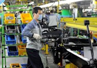 <p>This file photo shows workers of Ssangyong Motor working on the factory production line in Pyeongtaek, 70 km south of Seoul. South Korea's central bank cut its key interest rate by 25 basis points to 2.75 percent in response to a stronger-than-than-expected deceleration in economic growth.</p>