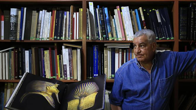 """In this June 18, 2015 photo, Zahi Hawass, Egypt's former head of antiquities, stands next to his new book, """"The legend of Tutankhamun,"""" as he speaks during an interview with The Associated Press in his office in Cairo. For more than a decade, he was the self-styled Indiana Jones of Egypt, presiding over its antiquities and striding through temples and tombs as the star of TV documentaries that made him an international celebrity. But four years after the 2011 uprising that toppled President Hosni Mubarak and nearly ended his own career, Hawass can be found in a cramped office, lamenting the state of the antiquities bureaucracy he once ruled like a pharaoh and dreaming of a new museum whose fate lies in limbo. (AP Photo/Hassan Ammar)"""