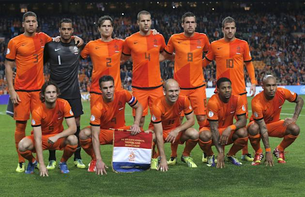 In this Oct. 11, 2013 file photo, Dutch soccer team poses prior the start the Group D World Cup qualifying soccer match between Netherlands and Hungary, at Arena stadium in Amsterdam, Netherlands. Bac