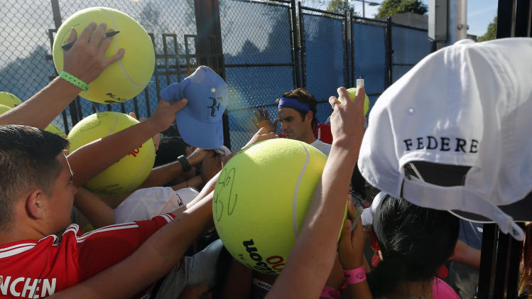 Roger Federer, of Switzerland, signs autographs for fans after practice at the 2014 U.S. Open tennis tournament, Friday, Aug. 29, 2014, in New York. (AP Photo/Elise Amendola)